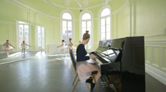 Sliding MLS Female Ballet Dancer sits playing the piano whilsta trio of young Ba Stock Footage