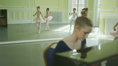 Sliding MS Female Ballet Dancer plays the piano whilst a trio of Dancers glide a Stock Footage