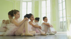 MLS Three Young Ballerinas crouch on the floor resting Stock Footage