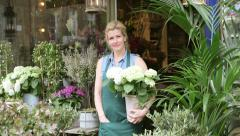 Upward Panning MLS A Florist stands in the doorway of her shop proudly Stock Footage