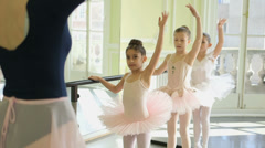 MS Female Ballet Dancer stands before a trio of Young Ballerinas demonstrating a Stock Footage