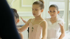 MCU Female Ballet Dancer stands before a trio of Young Ballerinas demonstrating  Stock Footage