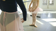 Upward Pan MCU Female Ballet Dancer stands before a Young Ballerina demonstratin Stock Footage