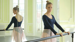 MLS Female Ballet Dancer stretches using the Studio Ballet barre Stock Footage