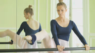 Stock Video Footage of MS Female Ballet Dancer stretches using the Ballet barre, then leans over it, re