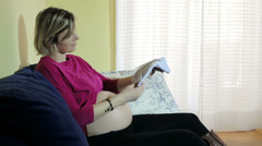 Beautiful pregnant lady is sitting on a sofa: belly, touch, clothes, baby, wait Stock Footage