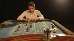 MS A Young Man sips his drink at the Roulette Table  Stock Footage