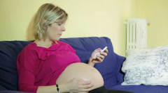 Pregnant woman close to giving birth making a call with mobile phone: smartphone - stock footage