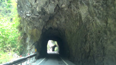 Driving on the mountain road and through tunnel of rock Stock Footage