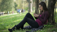 Stock Video Footage of woman types message lying down in the park: smartphone: mobile phone, outdoor