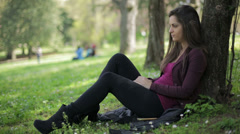 Cute woman in the park receive message on her smartphone: outdoor, mobile phone Stock Footage