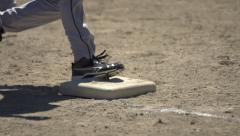 Slomo CU baseball base feet running on sunny day Stock Footage