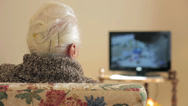 Stock Video Footage of old woman is watching tv: aged, ancient, older, watch, television, media, sofa
