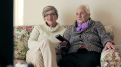 old woman is watching tv on  the sofa with her daughter: interior, old, aged, - stock footage