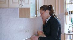 Beautiful business woman having breakfast in the kitchen - stock footage