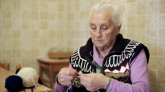 very old lady makes some home work: knit, wool, ancient,  aged,  - stock footage