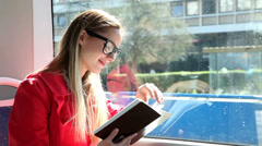 Cute blond woman reading book while riding tram, pointing on page Stock Footage