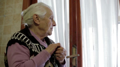 Very old woman praying at the window: god, cross, rosary Stock Footage