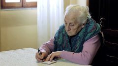 Old woman is writing on little notepad: pen, paper, older, ancient, notes, takes Stock Footage