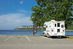 motorhome parked in a parking lot with sea in the background, georgian bay, t - stock photo