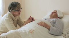 Woman at the bedside of a sick Senior: bed, illness, old, aged, worry, trouble Stock Footage