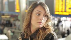 Young woman waiting for someone inside a railway station: trip, journey, crowd Stock Footage