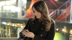 Young woman wearing coat walking in the shopping center using mobile phone - stock footage