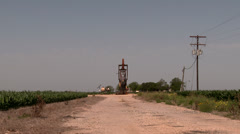 4K UHD Pumpjack drilling oil at end of dirt road Stock Footage