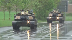 Us army tanks rolling down a wet road Stock Footage