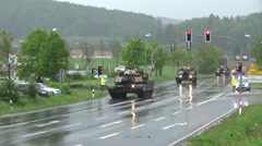 Us army tanks driving down public road Stock Footage