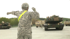 Us army soldier directs abrams tank into position Stock Footage