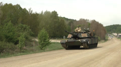 Us army abrams tank advancing on a dirt road Stock Footage