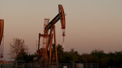 4K UHD 60fps Modern pumpjack pumping oil at sunset Stock Footage