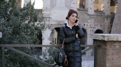 Young beautiful woman is talking at the phone in old city context: smartphone Stock Footage