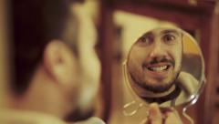 Strange man makes faces on a mirror: teeth, eyes, mad, madness, loneliness Stock Footage