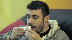 Sick man has a cold he is on an armchair sneezes: wipes his nose; handkerchief Stock Footage