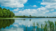 Time lapse 4k or HD - blue cloudy sky, lake, trees; zoom in Stock Footage