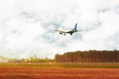 Airplane flying down near field and forest - stock photo
