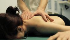 Therapist is doing a massage to a young cute girl: masseur; massaging Stock Footage