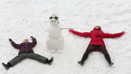 Stock Video Footage of Mother with daughter lie on the snow near snowman