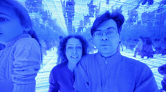 Family of three have fun in a mirrored room with blue lights Stock Footage
