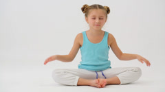 Girl doing is sitting with eyes closed in the lotus position Stock Footage
