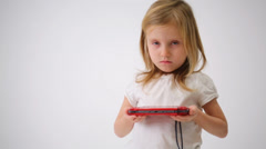 Cute little girl in white clothes holding red game controller Stock Footage