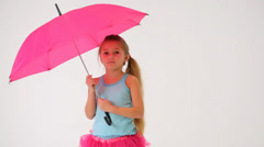 Cute little girl in cyan T-shirt with a pink umbrella Stock Footage
