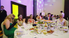 People at the table with glasses and snacks at masquerade ball Stock Footage