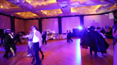 Couples dancing in purple light at masquerade ball Stock Footage