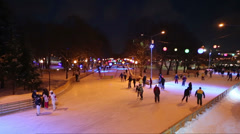 People are skating on evening rink with colored lamps Stock Footage