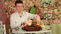 Man sits at table with beautiful flowers in basket Stock Footage