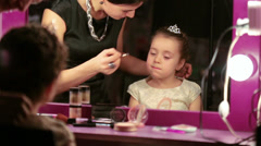 Mother makes makeup to little daughter reflected in mirror Stock Footage