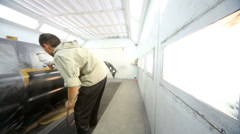 Stock Video Footage of Man paints car door with airbrush at paint-spray booth
